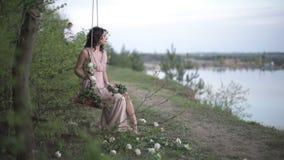 La muchacha sonriente muy hermosa en vestido rosa claro se relaja en el oscilación adornado por las flores en la playa del lago