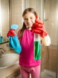 La muchacha sonriente que presenta con el paño y la despedregadora rocían en el cuarto de baño Fotografía de archivo libre de regalías