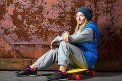 La muchacha sonriente que se sienta en penique plástico del color sube Fotografía de archivo