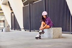 La muchacha sonriente que sienta las escaleras y pone pcteres de ruedas Imagen de archivo