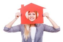 La muchacha sonriente que sostiene la casa de papel roja con el corazón forma Fotografía de archivo libre de regalías