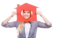 La muchacha sonriente que sostiene la casa de papel roja con el corazón forma Fotografía de archivo