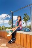 La muchacha sonriente que sostiene el monopatín y se sienta en parque Fotografía de archivo