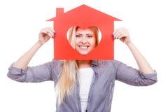La muchacha sonriente que sostiene la casa de papel roja con el corazón forma Fotos de archivo