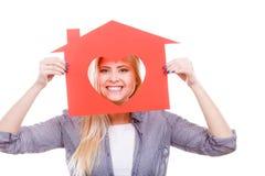 La muchacha sonriente que sostiene la casa de papel roja con el corazón forma Imagen de archivo