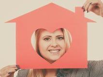 La muchacha sonriente que sostiene la casa de papel roja con el corazón forma Imagen de archivo libre de regalías
