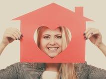 La muchacha sonriente que sostiene la casa de papel roja con el corazón forma Foto de archivo libre de regalías