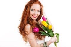 La muchacha sonriente Redheaded está sosteniendo tulipanes Fotografía de archivo libre de regalías