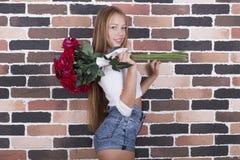 La muchacha sonriente rubia joven con las rosas rojas en vaqueros pone en cortocircuito Foto de archivo