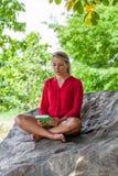 La muchacha sonriente 20s que lee un verano reserva debajo de un árbol Fotografía de archivo