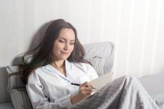 La muchacha sonriente satisfecha y feliz que miente en la cama en el cuarto y escribe un diario de sus sueños, planes, metas, exp Imágenes de archivo libres de regalías
