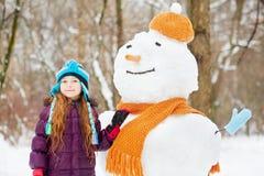 La muchacha sonriente se coloca al lado del muñeco de nieve en sombrero y bufanda anaranjados Fotografía de archivo