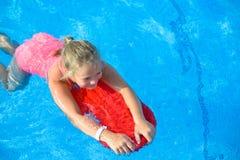 La muchacha sonriente se divierte con el tablero flotante en piscina Imagen de archivo