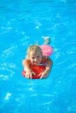 La muchacha sonriente se divierte con el tablero flotante en piscina Fotografía de archivo libre de regalías