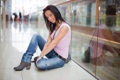 La muchacha sonriente se está sentando en la alameda de compras Imágenes de archivo libres de regalías