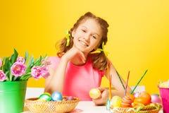 La muchacha sonriente se sienta en la tabla con los huevos de Pascua Foto de archivo