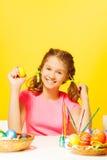 La muchacha sonriente se sienta en la tabla con los huevos de Pascua Imagenes de archivo