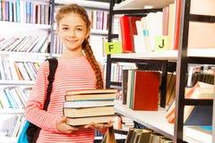 La muchacha sonriente sostiene los libros cerca de estante en biblioteca Fotos de archivo libres de regalías
