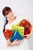 La muchacha sonriente sostiene los rectángulos con los regalos Imagen de archivo libre de regalías