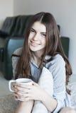 La muchacha sonriente tiene un té Imágenes de archivo libres de regalías