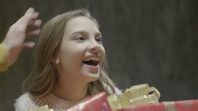 La muchacha sonriente toma la caja de Navidad de la familia de padres metrajes