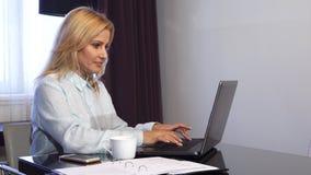 La muchacha sonriente trabaja detrás de su ordenador y hace una llamada video almacen de metraje de vídeo