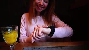 La muchacha sonriente utiliza el nuevo reloj elegante a mano almacen de video