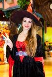 La muchacha sonriente vestida como bruja de Halloween que muestra la victoria gesticula Imagenes de archivo