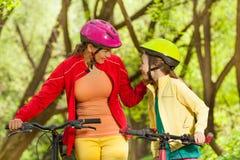 La muchacha sonriente y su mamá que completan un ciclo en primavera parquean Fotos de archivo