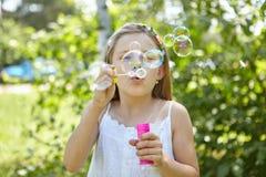 La muchacha sopla burbujas de jabón en el verano Imagen de archivo