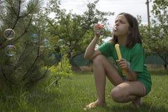 La muchacha sopla burbujas de jabón en un día soleado del verano Imagen de archivo