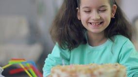 La muchacha sopla hacia fuera las velas en la torta almacen de metraje de vídeo