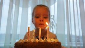 La muchacha sopla hacia fuera las velas en una torta de cumpleaños en honor de su cumpleaños almacen de video
