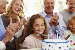 La muchacha sopla hacia fuera velas de la torta de cumpleaños en el partido de la familia imagen de archivo libre de regalías