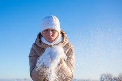 La muchacha sopla nieve ausente de las manos Imagen de archivo libre de regalías
