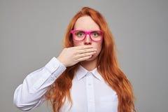 La muchacha sorprendente del pelirrojo cerró la boca con una mano Imagenes de archivo