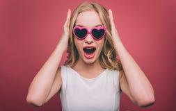 La muchacha sorprendente y atractiva lleva las gafas de sol Ella está pareciendo directa La persona femenina está llevando a cabo Imágenes de archivo libres de regalías