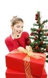 La muchacha sorprendida con los presentes acerca a un árbol de navidad Imagenes de archivo