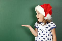 La muchacha sorprendida del niño con el sombrero de santa lleva a cabo su mano cerca del sc vacío imagen de archivo
