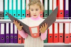 La muchacha sorprendida mira la carpeta y se coloca cerca a los estantes foto de archivo