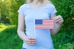 La muchacha sostiene la bandera de los E.E.U.U. en sus manos foto de archivo