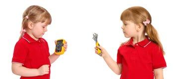 La muchacha sostiene a disposición un multímetro digital y una llave foto de archivo