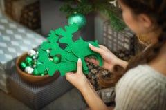 La muchacha sostiene a disposición una decoración de la Navidad de ciervos verdes Fotografía de archivo libre de regalías