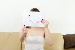 La muchacha sostiene el índice y el smiley se ahoga en el papel Fotografía de archivo libre de regalías