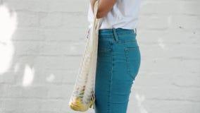 La muchacha sostiene el bolso de compras hecho punto secuencia reutilizable de la malla con las frutas y verduras almacen de metraje de vídeo