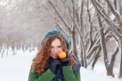 La muchacha sostiene el mandarín en el día de invierno Imagen de archivo