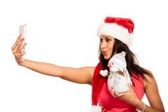 La muchacha sostiene el muñeco de nieve que toma el selfie Imágenes de archivo libres de regalías