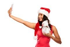 La muchacha sostiene el muñeco de nieve que toma el selfie Foto de archivo