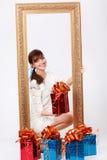 La muchacha sostiene el rectángulo con el regalo y mira hacia fuera de marco imagen de archivo