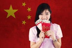 La muchacha sostiene el sobre con el fondo chino de la bandera Fotografía de archivo libre de regalías